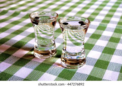 Two glasses with sambuca on a table with a white-green checkered tablecloth.
