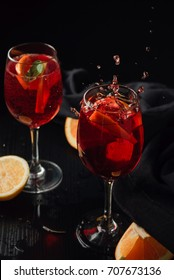 Two glasses of sangria with citrus and fresh mint. Splash of drink. Black background. Close up.