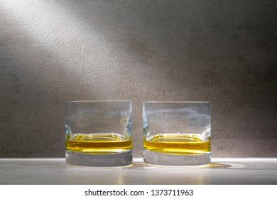 Two glasses of scotch whiskey on gray background