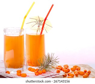 Two glasses with sea buckthorn fruit drink and sea-buckthorn berries