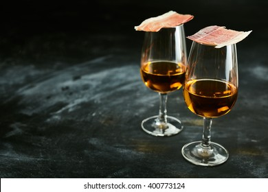 Two glasses of Spanish sherry served with slices of speciality smoked ham for traditional tapas over a slate background with copy space