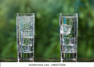 two glasses of sparkling water and with ice cubes, on a background of greenery, gas bubbles and spray