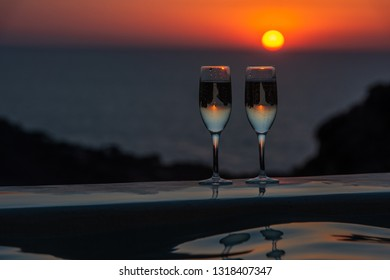 Two glasses of sparkling wine by the pool on a sunset background.