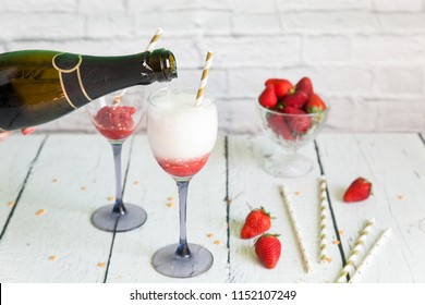 Two glasses of sparkling wine cocktail with strawberry sorbet. New years eve celebration. Wineglasses with champagne and gold paper straws for wedding party. Pouring wine into glasses with granita