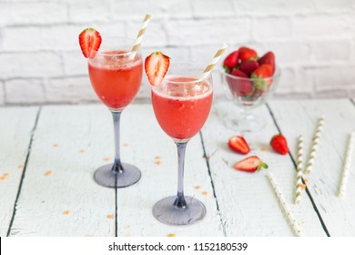 Two glasses of sparkling wine cocktail with strawberry sorbet. New years eve celebration. Wineglasses with champagne and gold paper straws for wedding party