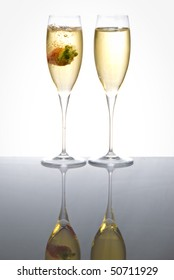 Two glasses of sparkling wine with a floating strawberry