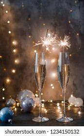 Two glasses of sparkling wine with sparklers. Dark background with yellow light bokeh. Christmas tree toys on the table.
