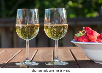 Two glasses sparkling wine and strawberries  on a wooden table in late evening sunshine