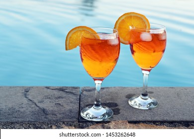 two glasses Spritz Veneziano, an Italian cocktail drink from aperol, prosecco and soda, served at the pool, copy space, selected focus