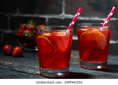 two glasses of strawberry lime lemonade on a dark wooden background, closeup horizontal