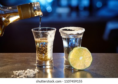 Two glasses with a tequila and a slice of lime, gold and silver on the background of a bar with a beautiful backlight. The process of pouring a golden tequila into a glass from a bottle.