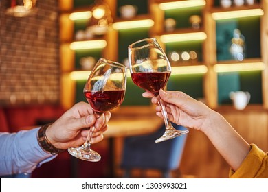 Two glasses together. Close-up of couple holding red wine in restaurant