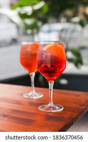 Two glasses if traditional Italian cocktail on a wooden table in an outdoor cafe