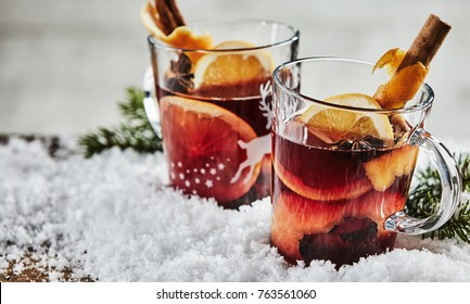 Two glasses of traditional spicy Christmas mulled hot Gluhwein with orange, cinnamon and star anise on fresh winter snow in a close up view