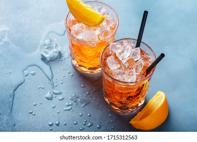 Two glasses of a traitional Italian cocktail aperrol spritz with orange and ice. Selective focus imge with a copy space for your text.