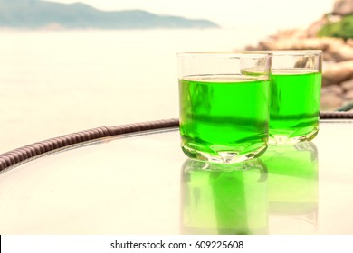Two glasses of transparent green juice on the table near the sea.