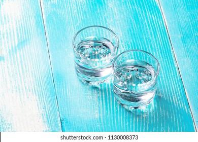 two glasses under the alcohol in the middle of the frame, a background of blue painted wood