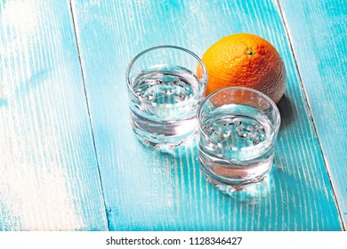 two glasses of vodka on a wooden table painted in blue, next to the glasses is citrus