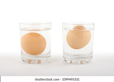Two glasses of water with a fresh egg on the left and a rotten egg on the right side on white background. Bad egg floats in water.