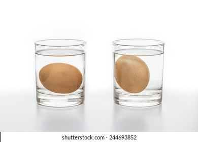 Two glasses of water with a fresh egg on the left and a rotten egg on the right side isolated on white background