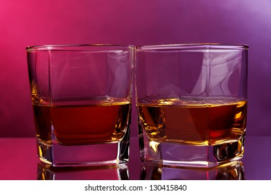 two glasses of whiskey against warm backdrop