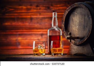 Two glasses of whiskey, bottle and keg with ice cubes served on wooden planks with keg. Vintage countertop with highlight and a glass of hard liquor
