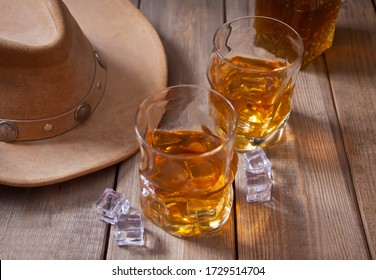 Two glasses of whiskey and cowboy hat on the old wooden table with bottle on the backgrounds.