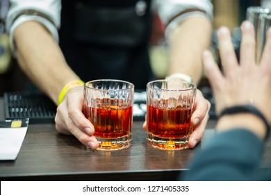 Two glasses of whiskey in the hands of a bartender