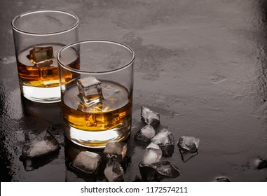 Two glasses of whiskey with ice cubes on black background with reflection, relaxation drink for two, copy space