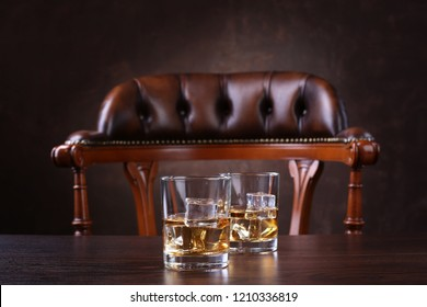 Two glasses of whiskey with ice cubes on wooden table