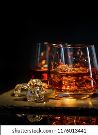 Two glasses of whiskey with ice on a black background.