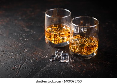 Two glasses of whiskey with ice on dark background with reflection. Alcohok drink. Space for text.