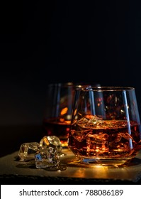 Two glasses of whiskey with ice on a black background