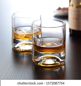 Two glasses of whiskey with ice served on wooden table
