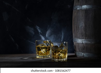 Two glasses of whiskey with ice and wooden barrel on marble background