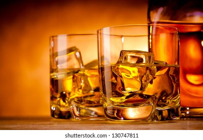 Two glasses of whiskey on the rocks and a bottle