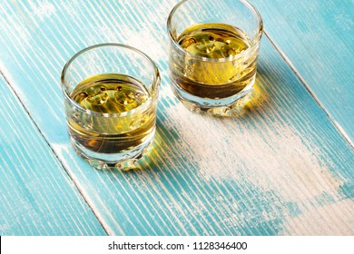 two glasses of whiskey on a wooden table blue, brown on blue