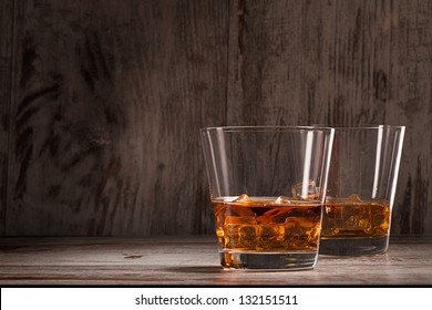 two glasses of whiskey over wooden background