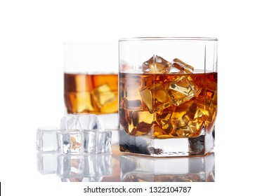 Two glasses of whisky with ices on a white background with reflection.