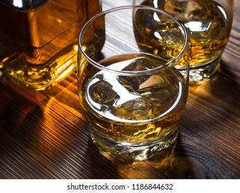 Two glasses of whisky on the rocks and a bottle