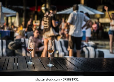 Two glasses of white or red vine against group of people. Hot beach party. Sexy people