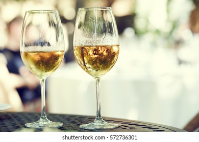 two glasses of white whine outdoors