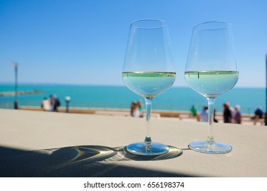 Two glasses of white whine over the sea