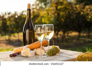 Two glasses of white wine and bottle at sunset