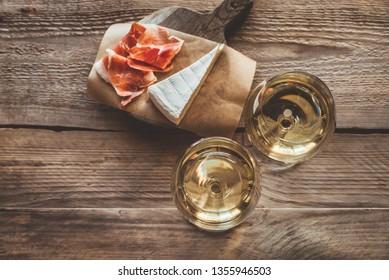 Two glasses of white wine with Brie and Prosciutto ham