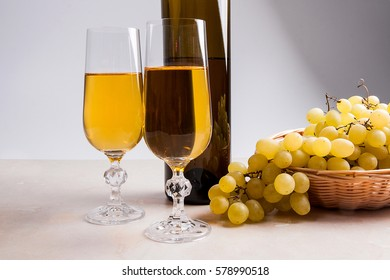 Two glasses with white wine and brown bottle of white wine on light marble background. Bunch of green grapes in yellow wooden basket near the glasses.