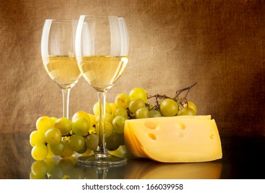 Two glasses of white wine, a bunch of white grapes and cheese on linen background