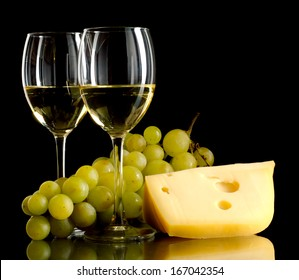 Two glasses of white wine, a bunch of white grapes and cheese on black background