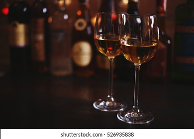 Two glasses of white wine Chardonnay in a bar or restaurant in the background bottles with alcohol. Bar interior background, place for text