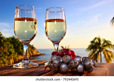 Two glasses of white wine and Christmas ornament on the sea and sky background, shallow focus